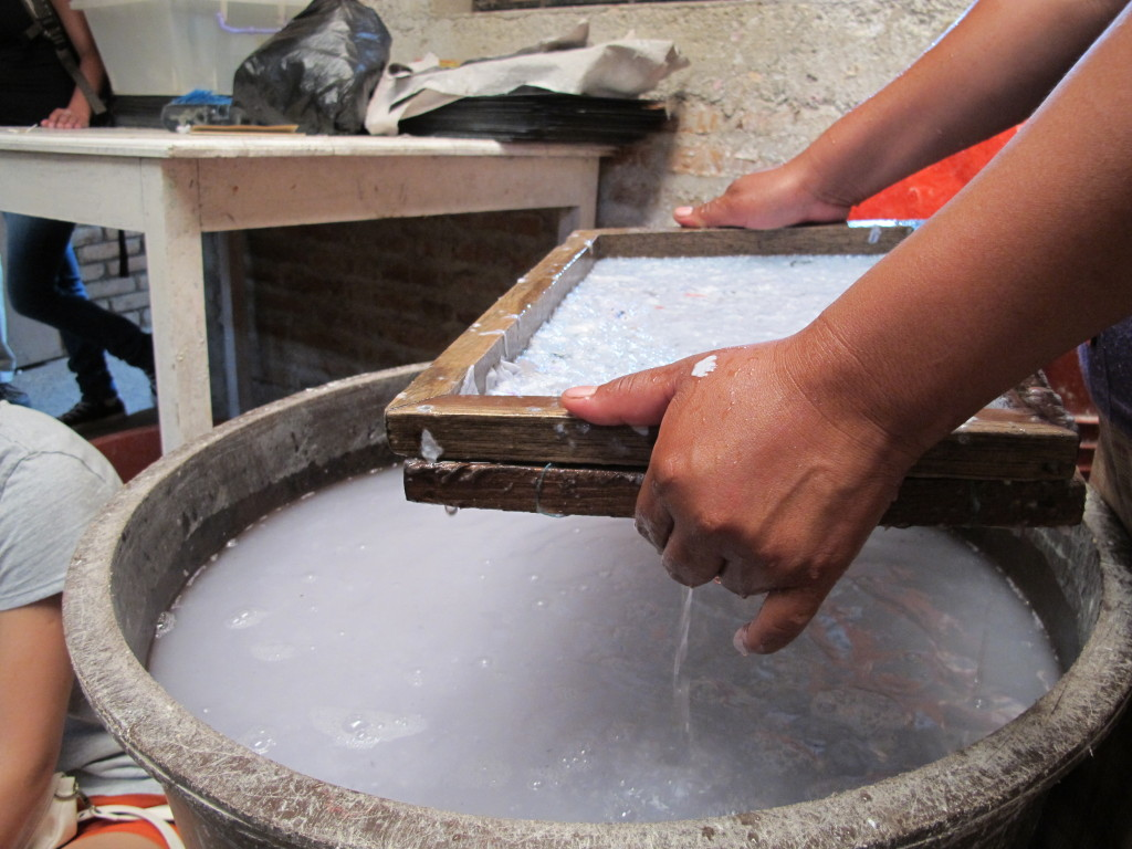 An employee demonstrates the paper making process for a visiting service group.